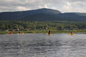 Family and friends canoe and kayak trip across Big Tupper Lake, back to Camp Wilderness Sunrise & Moon Cottage